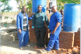 Aaron Maluwa (center) with the plumbers who installed the SkyHydrant.